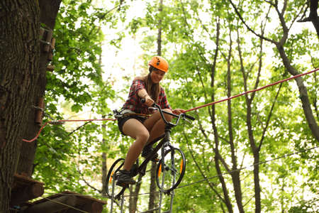 MOSCOW - SEPTEMBER 11: Girl riding bicycle on tightrope, on September 11, 2010 in Moscow, Russia. First time in Moscow rope adventure park Panda Park was opened at September 2010.