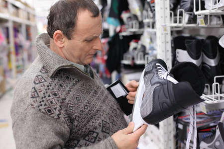 elderly man in gray sweater chooses skates in big sports shop photo