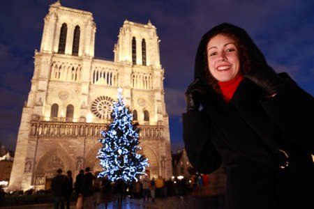 prayer tower: Young smiling woman stands on the square in front of  Notre Dame Cathedral and Christmas tree in the evening in Paris.