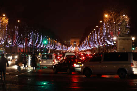 champs: Paris at night. View of the Triumphal Arc on the square of Charles de Gaulle from the Champs-Elysees. Focus on Arc. Editorial