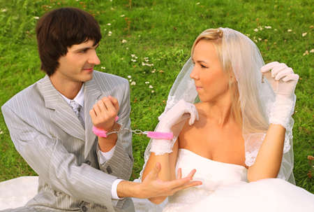 woman handcuffs: Beautiful young groom and bride wearing white dress sitting on green grass and handcuffed,  groom ask of bride key
