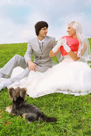 Beautiful young groom and bride wearing white dress sitting on green grass; bride keeps heart-shaped red balloon; small dog lies near couple photo