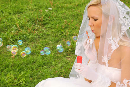 blubber: Beautiful young bride wearing white dress sitting on green grass and blowing bubbles