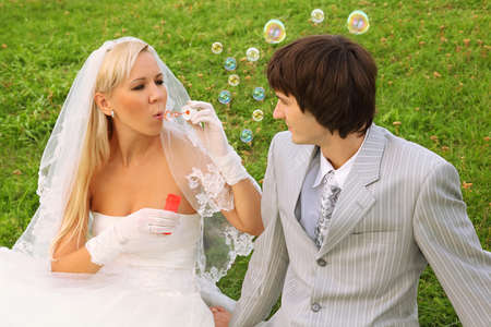 Beautiful young bride wearing white dress sitting on green grass with groom and blowing bubbles; focus on man photo