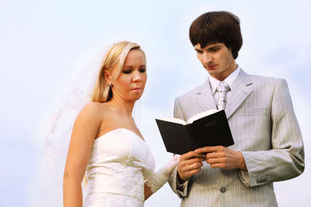 Beautiful young groom and bride wearing white dress read Bible together photo