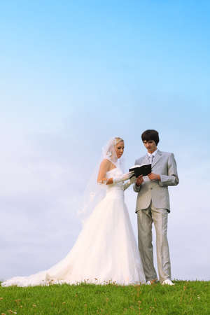 Beautiful young groom and bride wearing white dress read Bible together on green field photo