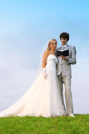 Beautiful young groom and bride wearing white dress read Bible together on field photo
