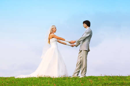 Beautiful young groom and bride wearing white dress standing on green grass and holding hands photo