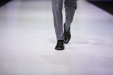 fashion catwalk: foot of male model in gray trousers and black shoes on catwalk