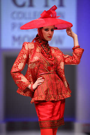 defile: MOSCOW - FEBRUARY 22: Woman wear red suit and hat from Slava Zaytzev walk the catwalk in the Collection Premiere Moscow, a fashion industry platform of IGEDO Company, on February 22, 2011 in Moscow, Russia.