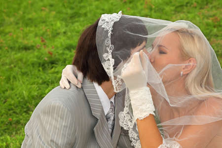 Beautiful young groom and bride wearing white dress hidden under veil and kiss on green field photo