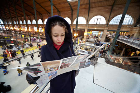 explores: PARIS - DECEMBER 31: Young woman explores the map of Paris on the second floor of the station Gare de Est. The right side of the station is on the background, December 31, 2009, Paris, France. Gare de Est - Eastern Railway Station of Paris.