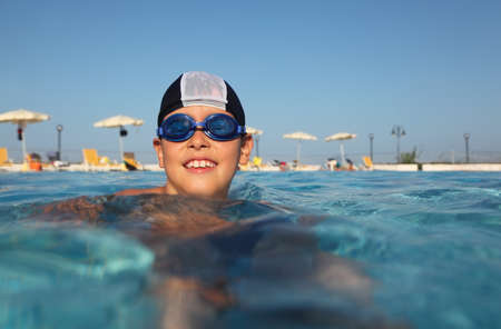 little boy with glasses for swimming and bathing cap, swim in pool. in background beach umbrellas. from the underwater package photo