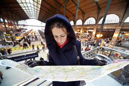 PARIS - DECEMBER 31: Young woman explores the map of Paris on the second floor of the station Gare de Est, December 31, 2009, Paris, France. Gare de Est - Eastern Railway Station of Paris, one of six large Parisian railway stations of the National Company Stock Photo - 17654278