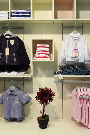 clothing store: children clothing store, clothing on shelves, hangers with jackets, artificial tree
