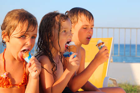 woman with ice cream: little brother and two sisters in swimsuits on beach eating ice cream after bath. focus on girl in middle