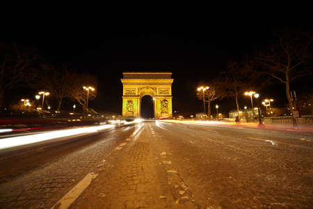 triumphal: Brightly illuminated Triumphal Arch and color traces of the cars at night. Stock Photo