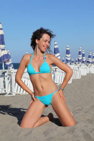 beautiful young woman in blue swimsuit kneeling on beach. in background rows of white deck chairs and beach umbrellas photo