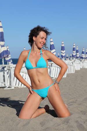 mujer arrodillada: joven y bella mujer en traje de baño azul de rodillas en la playa. en las filas de fondo de tumbonas y sombrillas blancas