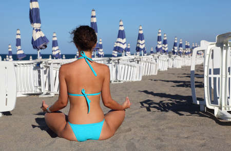 beautiful young woman in blue swimsuit seats on beach. in background rows of white deck chairs and beach umbrellas photo