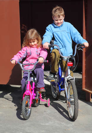 little brother and sister ride children's bicycles. girl in pink jacket, boy in blue jacket photo