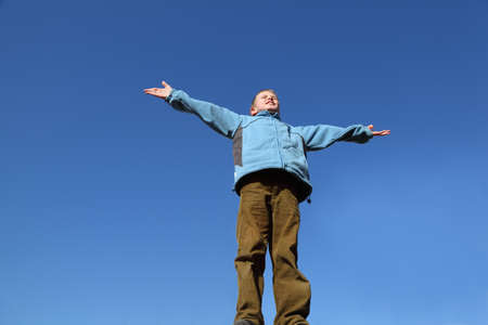 raises: little boy in blue jacket and brown pants raises his arms to blue sky Stock Photo