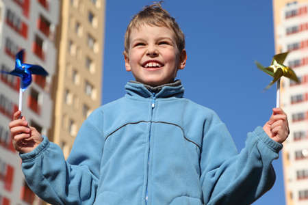 pinwheels: little boy in blue jacket with pinwheels in his hands. In background of multi-storey yellow house