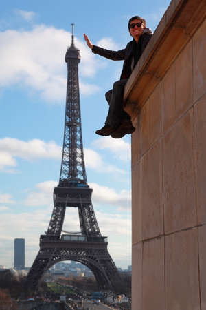 tonnes: PARIS - JANUARY  2: Man in sunglasses sitting on wall, poses, pretending that touches Eiffel Tower on January 2, 2010 in Paris. Weight of Eiffel Tower is 10 100 tonnes Editorial