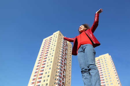 house coats: beautiful young woman in red jacket and blue jeans raises his hands to sky. in background two multi-story yellow house Stock Photo