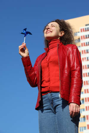 beautiful young woman in red jacket and blue jeans playing with blue spinner. in background yellow multi-storey building photo