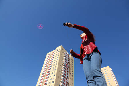 beautiful young woman in red jacket and blue jeans playing with pink propeller. two yellow blocks of flats photo