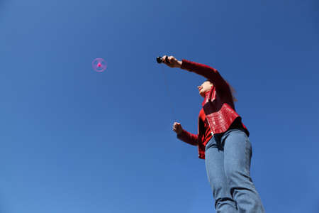 beautiful young woman in red jacket and blue jeans playing with pink propeller photo