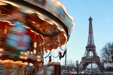 avocation: Vintage carousel with white horses spins, Eiffel tower in Paris, France