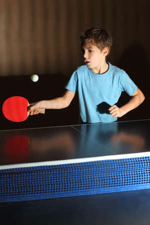 little boy wearing blue shirt playing table tenis, concentrated face, blue net photo