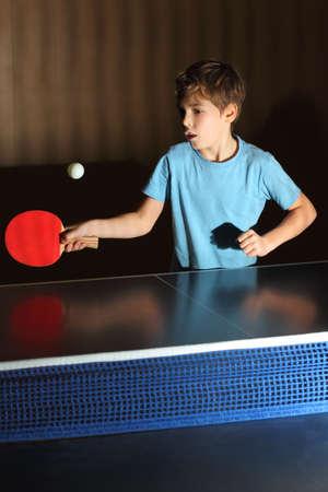 ping pong: niño pequeño que desgasta la camisa azul jugando tenis de mesa, la cara concentrada, neto azul