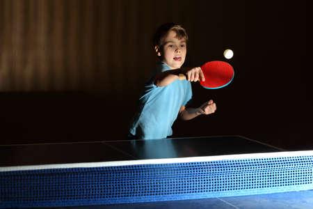 テーブル テニス、青いシャツを着て小さな男の子集中顔、舌を彼の少年