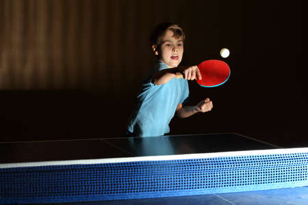 little table: little boy wearing blue shirt playing table tennis, concentrated face, boy stuck out his tongue