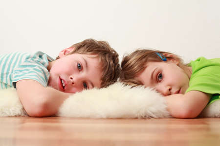 little brother and sister lying on floor on white skin and look at camera, focus on boy Standard-Bild