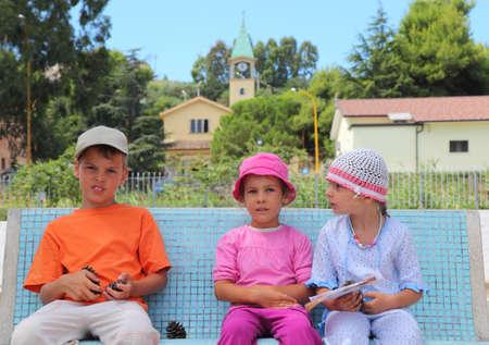 familia en la iglesia: pequeño hermano y dos hermanas se están sentando en el banco azul. muchacho que sostiene cono. en el fondo de la iglesia italiana Foto de archivo