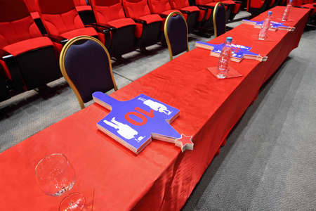 concurrence: Long judge table with  red table-cloth on which cards lie stands in empty hall Stock Photo