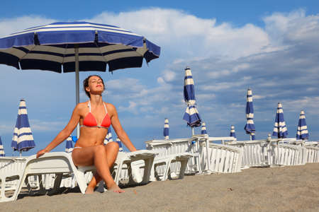 loungers: beautiful young woman in bathing suit sitting on white chaise lounge and sunbathe, rows of white loungers and blue umbrellas