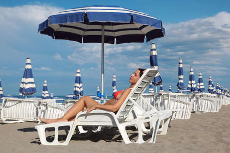 beautiful young woman lying on lounger under beach umbrella and sunbathe. in background rows of white loungers and blue umbrellas photo