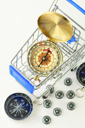exactness: big golden compass in cart and ten black compasses isolated on white