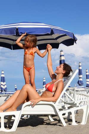sunbath: jonge moeder liggend op ligstoel onder parasol. dochtertje in badpak staan in de buurt moeder en houdt haar hand
