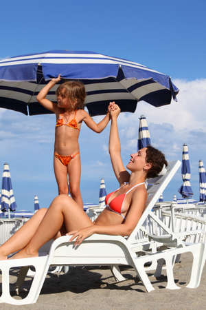 beautiful preteen girl: young mother lying on lounger under beach umbrella. little daughter in bathing suit standing near mother and holds her hand Stock Photo