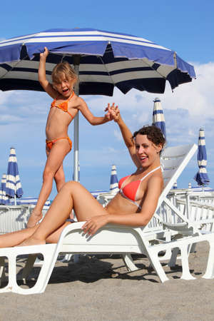 preteens beach: young mother lying on lounger under beach umbrella. little daughter standing near mother and holds her hand