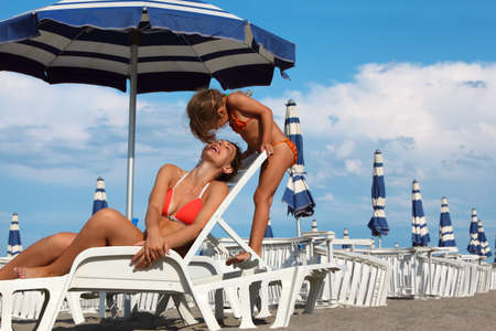 lounger: young mother lying on lounger under beach umbrella. little daughter in bathing suit standing near mother