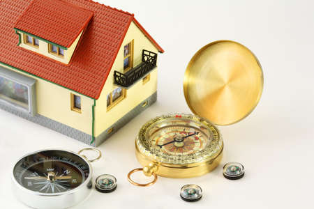 exactitude: toy house with red roof and seven different compasses isolated on white Stock Photo