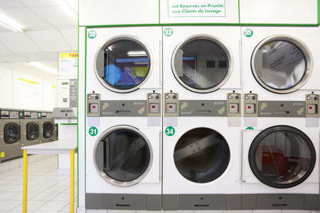 cleanly: number of white and gray washing machines in empty public laundry