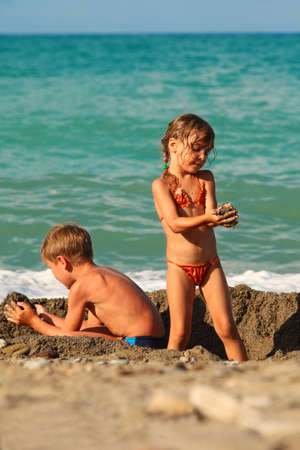 little brother and sister playing in sand after swim at beach Standard-Bild